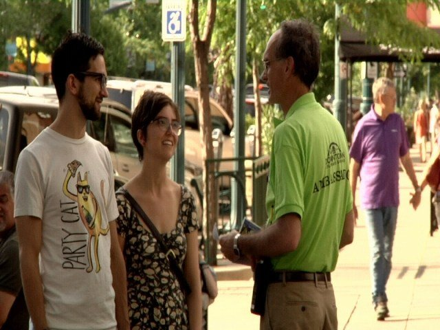 Colorado Springs Ambassador volunteer Dean Strain speaks with a couple along Tejon Street on Saturday June 11, 2016