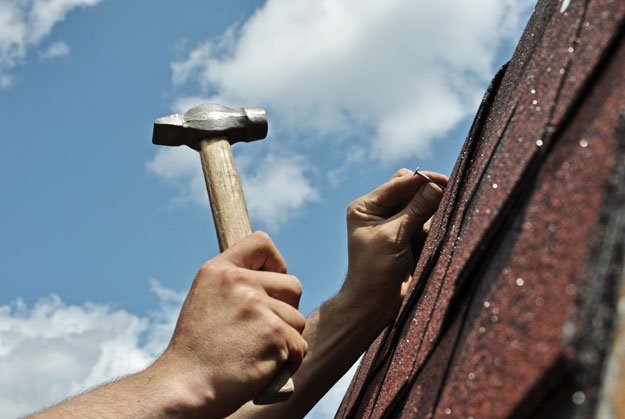 hammering roofing nails into shingles
