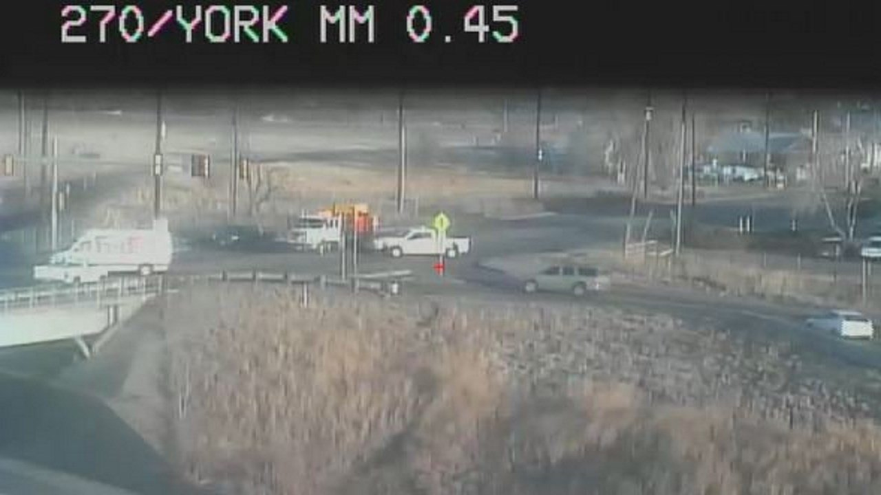 Traffic cam view of crash scene in Denver where a car went off an interstate overpass.