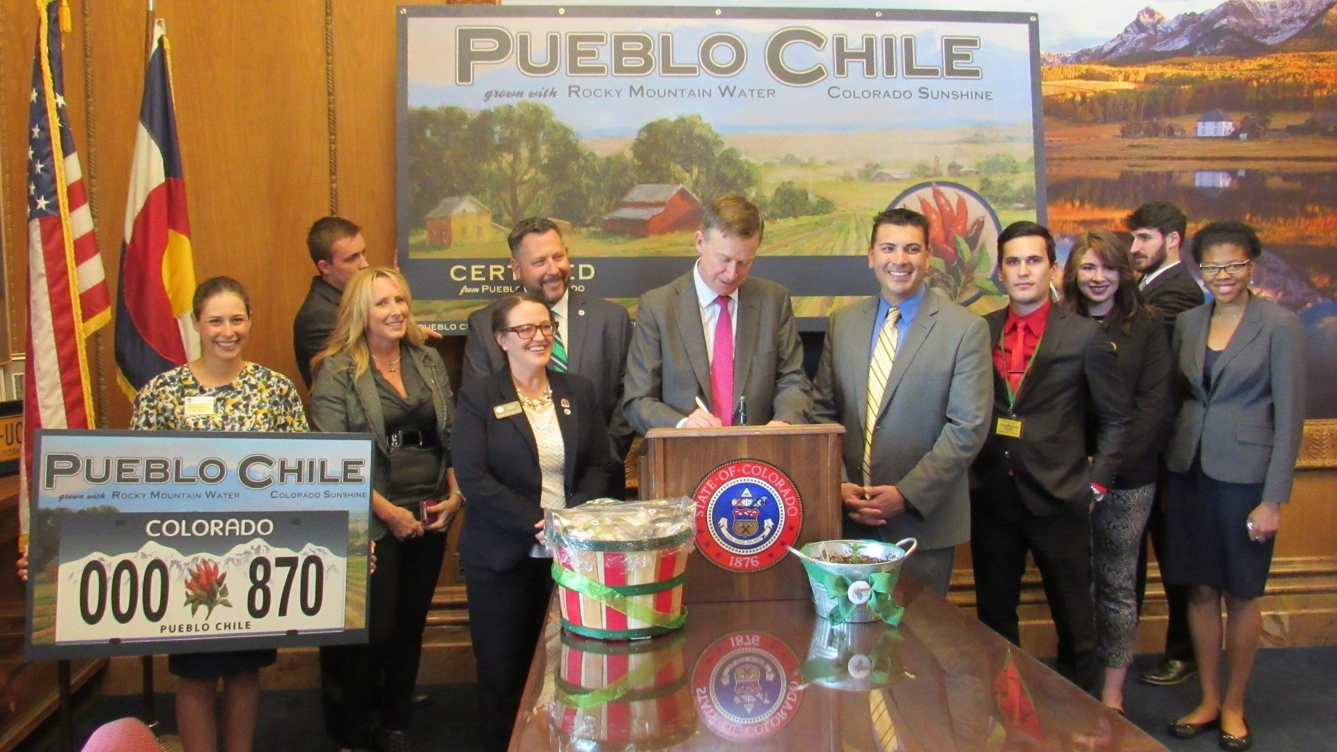 Flanked by Rep. Daneya Esgar, D-Pueblo, and Sen. Leroy Garcia, D-Pueblo, Gov. John Hickenlooper signs their bill to create the Pueblo Chile license plate. Rep. Esgar's aide, Amy Johnson, holds a rendering of the plate.