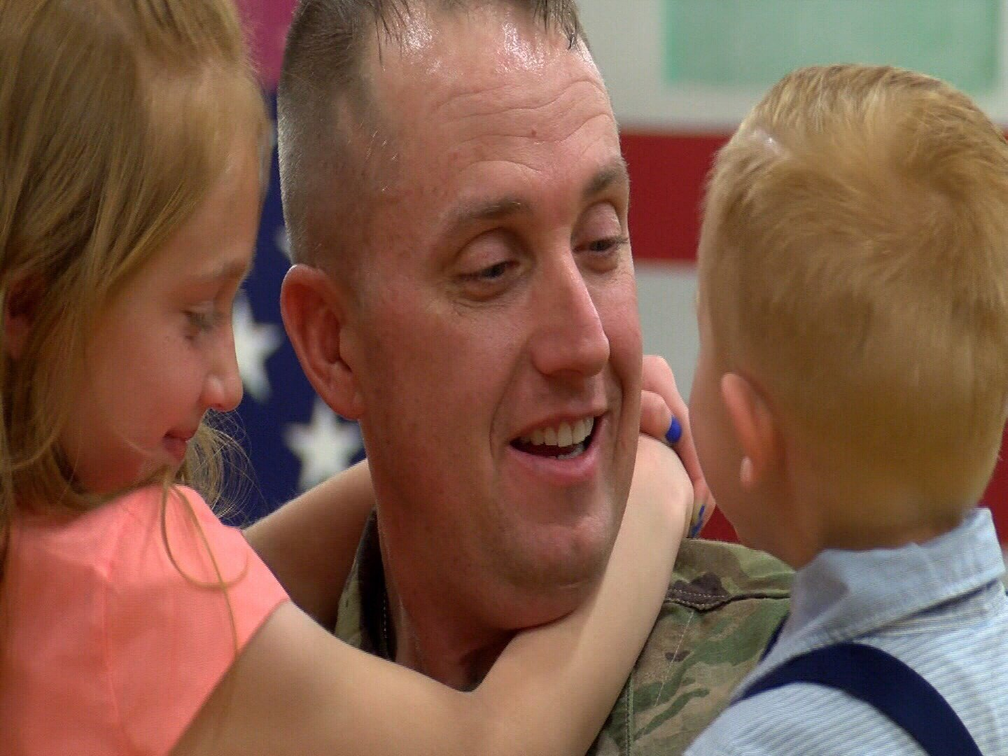 Capt. Seth Peters holds two of his kids after being welcomed home to Fort Carson on Monday night. (KOAA)