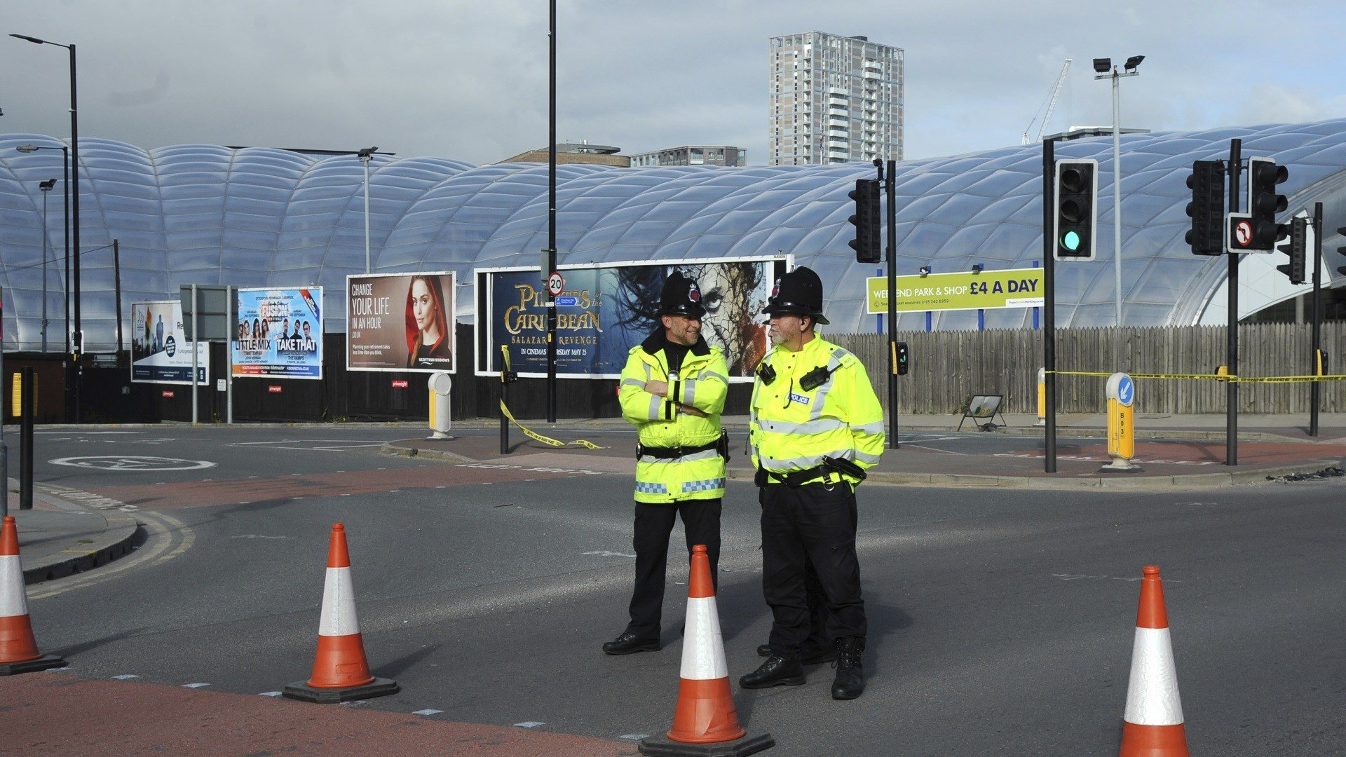 Police block a road outside the Manchester Arena in central Manchester, England Tuesday May 23, 2017. An apparent suicide bomber set off an improvised explosive device that killed over a dozen people at the end of an Ariana Grande concert on Monday, Manch