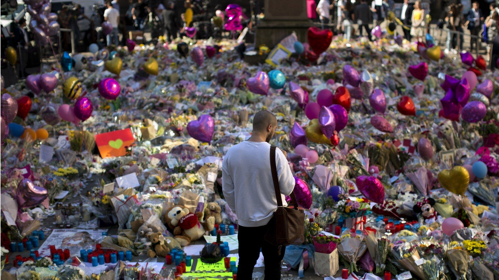A man stands next to flowers for the victims of Monday's bombing at St Ann's Square in central Manchester, England, Friday, May 26 2017. British police investigating the Manchester Arena bombing arrested a ninth man while continuing to search addresses as