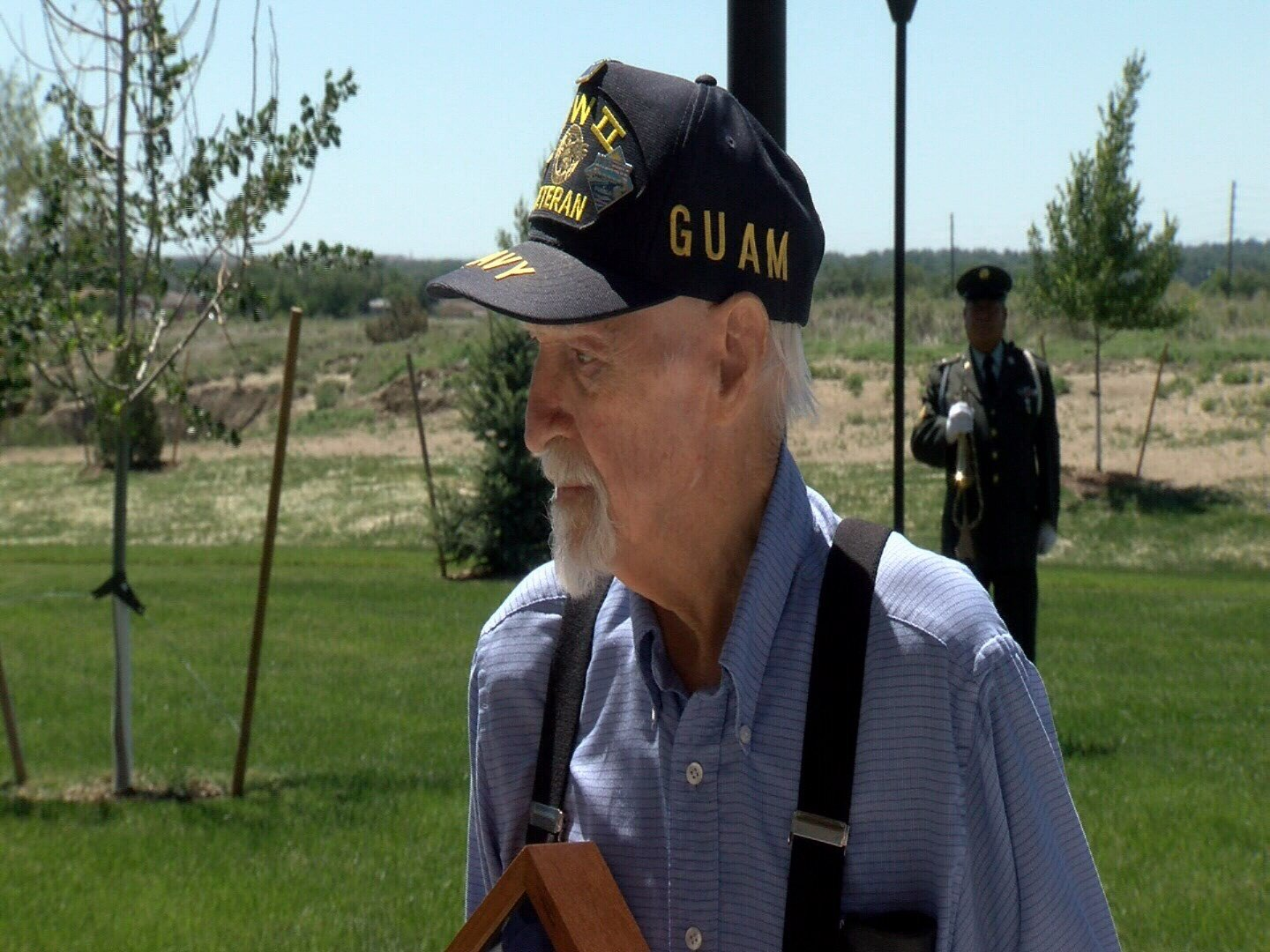 Veteran Ken Carter of Pueblo holds a flag during presented to him during ceremony Friday