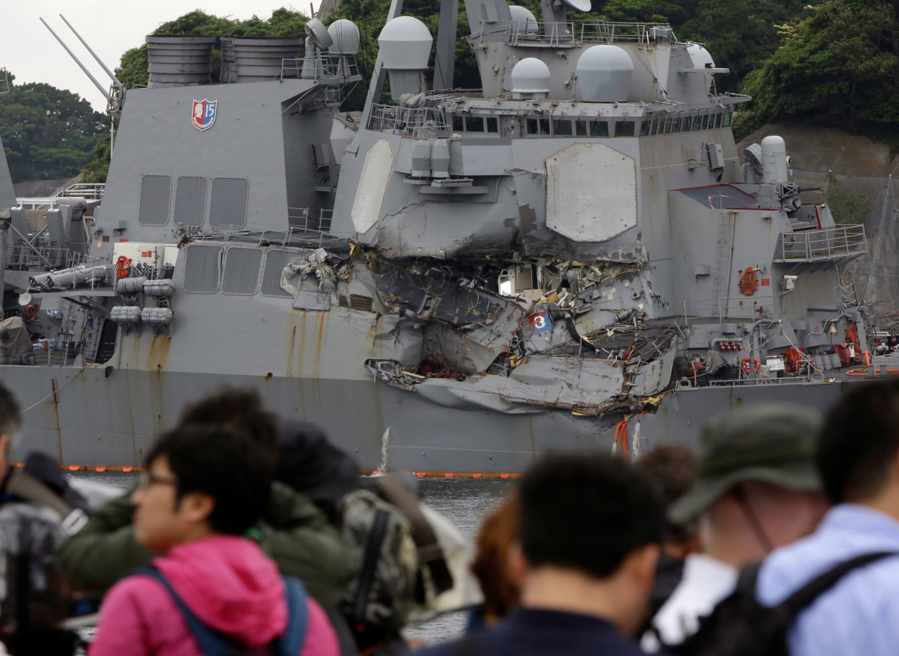 Journalists observe the damaged USS Fitzgerald at the U.S. Naval base in Yokosuka. Navy divers found sailors' bodies Sunday aboard the USS Fitzgerald that collided with a container ship in the busy sea off Japan. (AP Photo/Eugene Hoshiko)