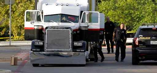 San Antonio police officers investigate the scene where eight people were found dead in a tractor-trailer loaded with at least 30 others outside a Walmart store on Sunday, July 23, 2017, in San Antonio, Texas.