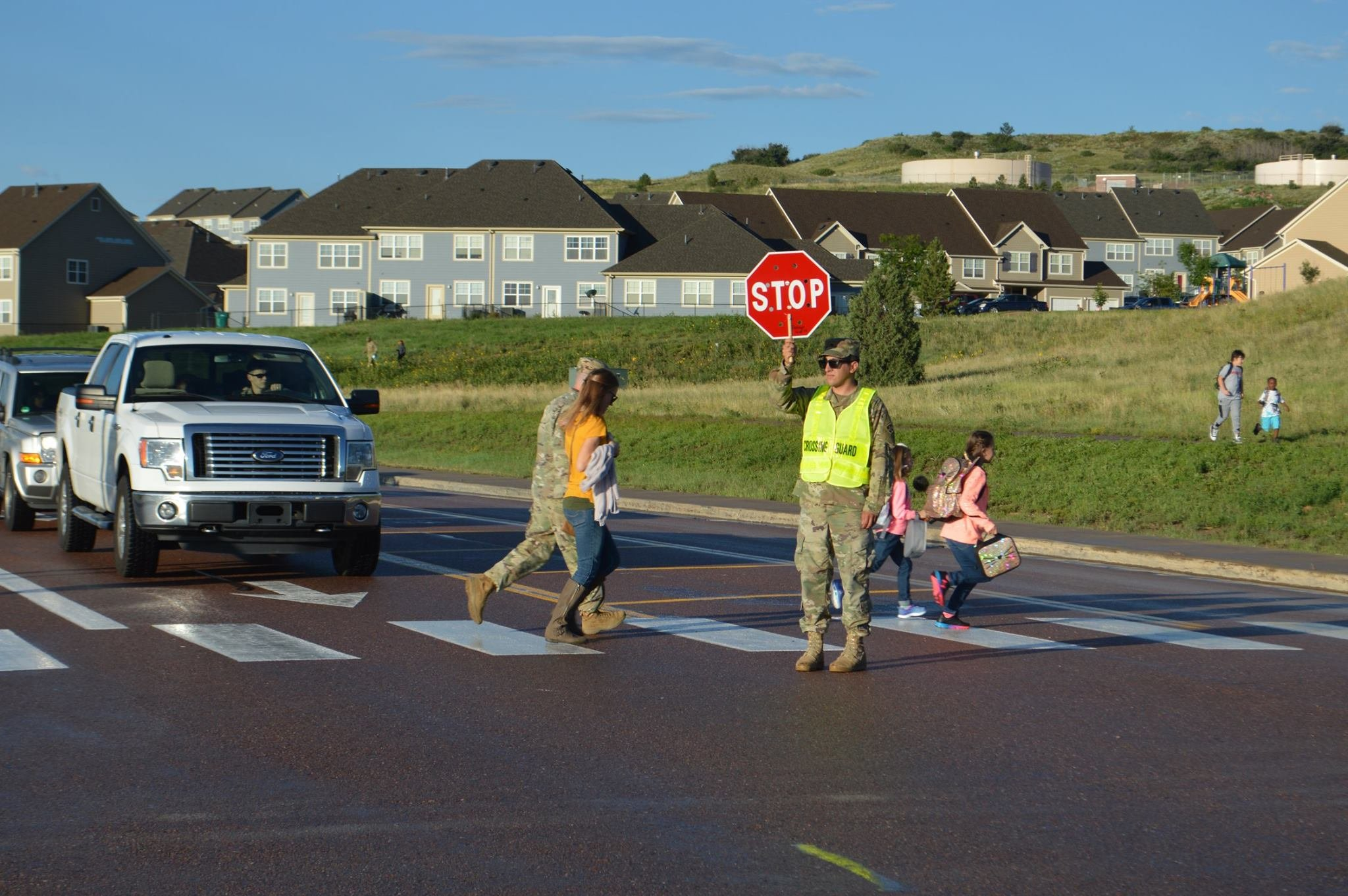 Spc. Christian Betancourt, Headquarters and Headquarters Company, 4th Sustainment Brigade, 4th Infantry Division, stops traffic at one of Fort Carson's school-zone crosswalks. Fountain-Fort Carson District 8 schools started the 2017-18 school year today.