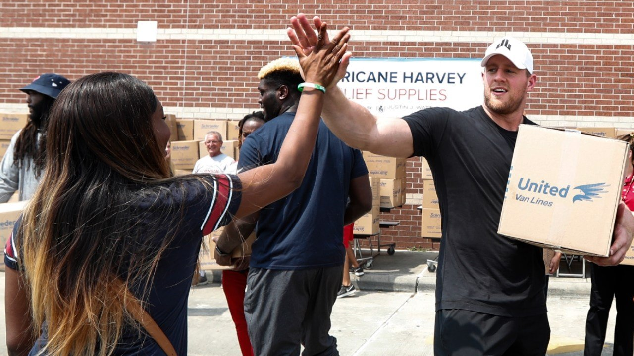 Anna Ucheomumu, left, high fives Houston Texans defensive end J.J. Watt after loading a car with relief supplies to people impacted by Hurricane Harvey on Sunday, Sept. 3, 2017. (Brett Coomer/Houston Chronicle via AP, Pool)