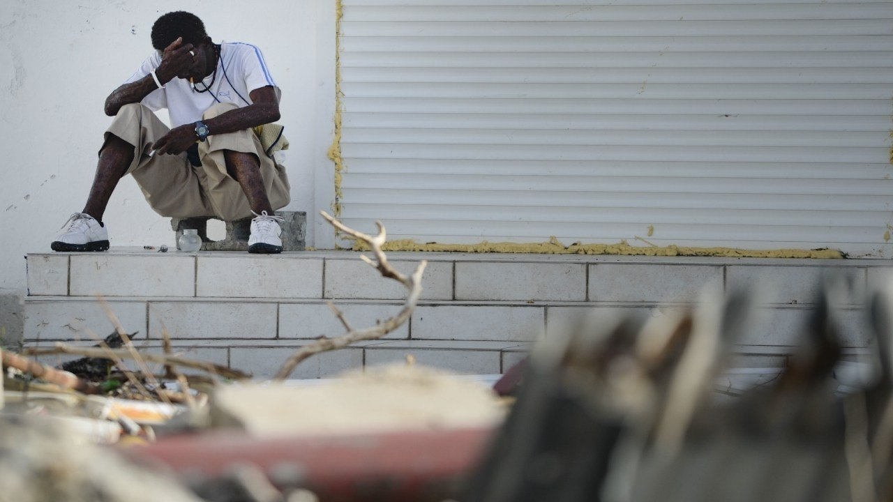 A sits on a porch on the destroyed Philipsburg after the passing of Hurricane Irma in St. Martin, Monday, September 11, 2017. (AP Photo/Carlos Giusti)