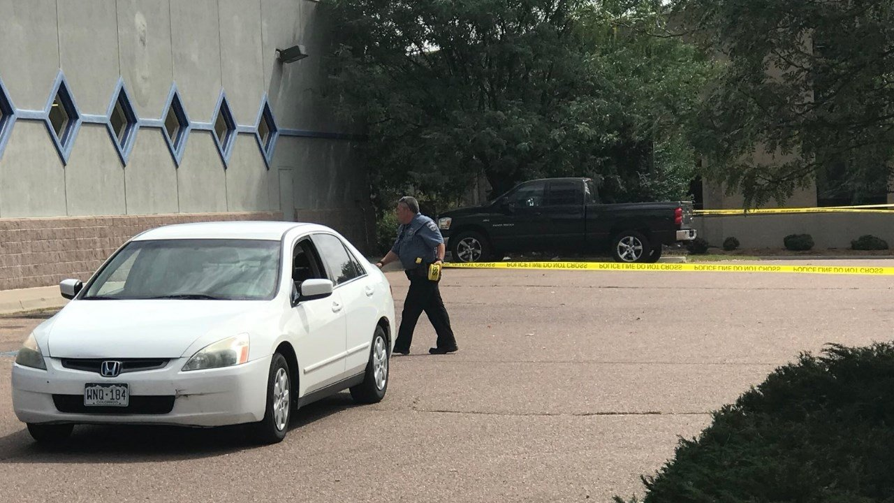 An officer places crime scene tape at the shooting scene near Doherty High School. (KOAA)