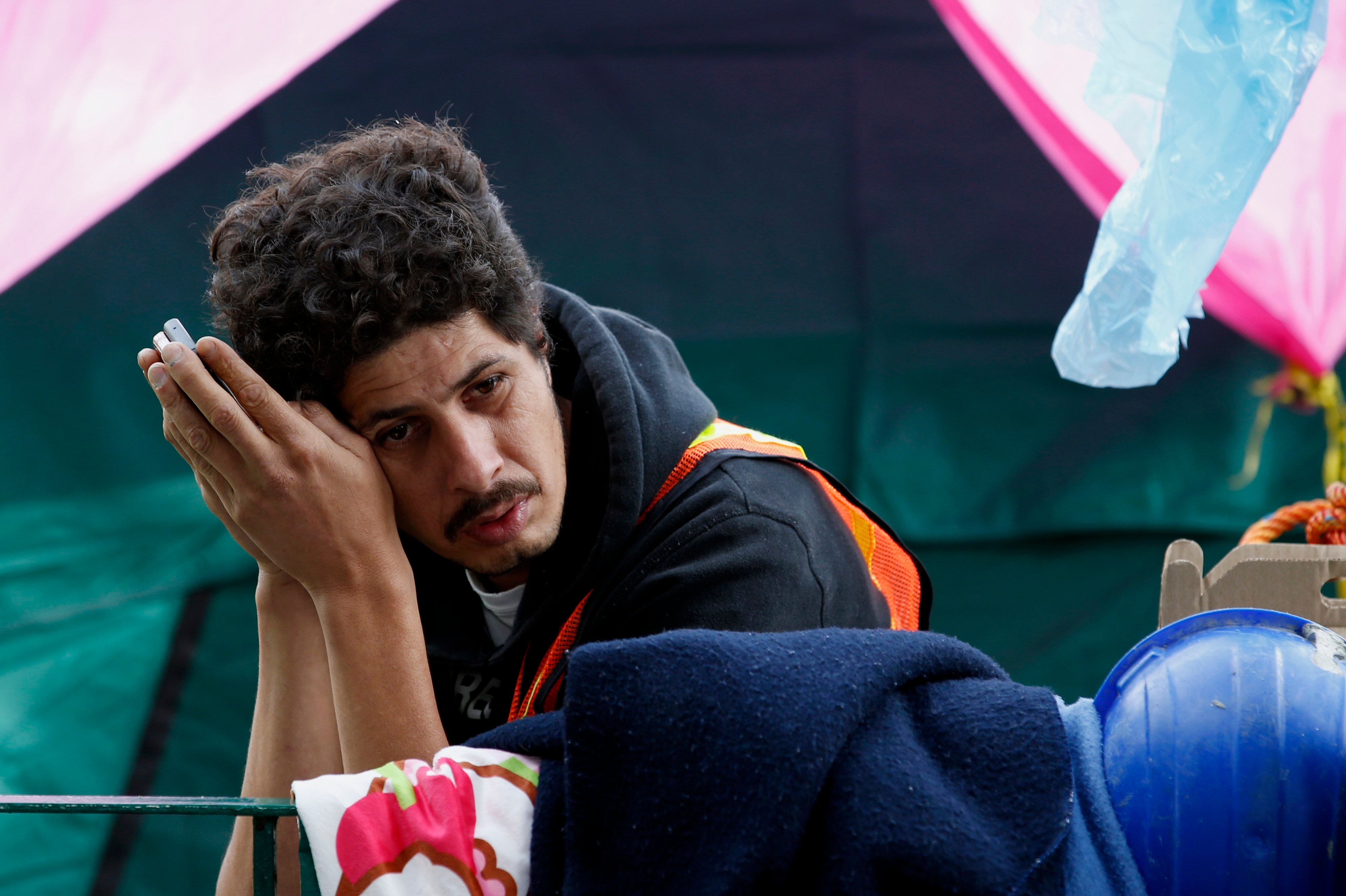Pablo Vega Rodríguez listens to his mobile as he waits for news on his cousin Paulino Estrada, at an ad-hoc camp outside a quake-collapsed seven-story building where Estrada is believed to be trapped, in Mexico City's Roma Norte neighborhood, Friday, Sept