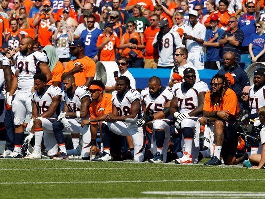 Denver Bronco players kneel in protest during the National Anthem before a game against the Buffalo Bills at New Era Field.