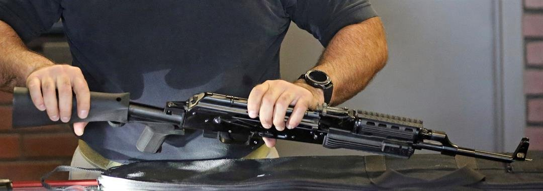 Clark Aposhian, chairman of the Utah Shooting Sports Council, attaches a little-known device called a bump stock to a semi-automatic rifle at the Gun Vault store and shooting range Wednesday, Oct. 4, 2017, in South Jordan, Utah.
