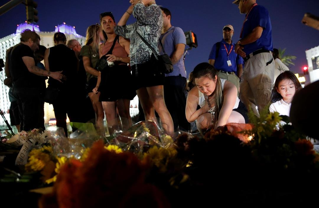 People pause at a memorial set up for victims of a mass shooting in Las Vegas, on Tuesday, Oct. 3, 2017. A gunman opened fire on an outdoor music concert on Sunday. It was the deadliest mass shooting in modern U.S. history.