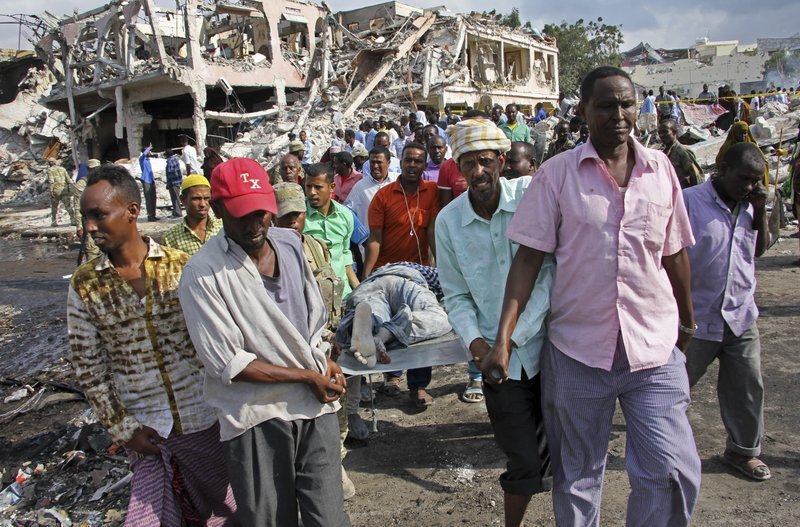 Somalis remove the body of a man killed Saturday in a truck bombing in Mogadishu