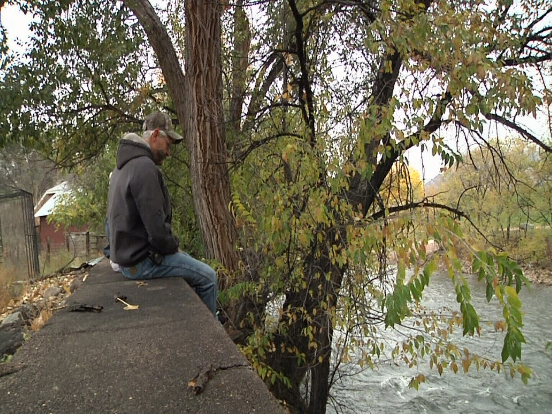 Dennis & Nancy Brady sit on concrete wall on Arkansas River near their property