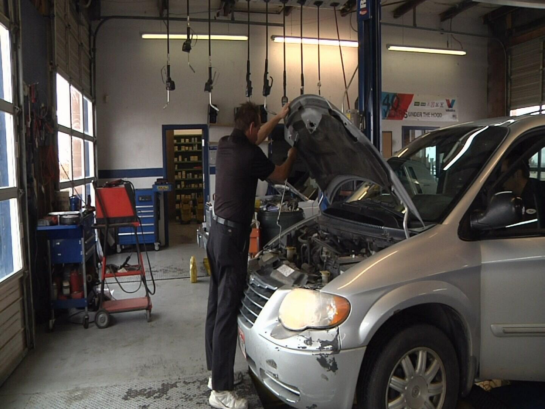 Service Writer Joseph Lauricella opens hood of car