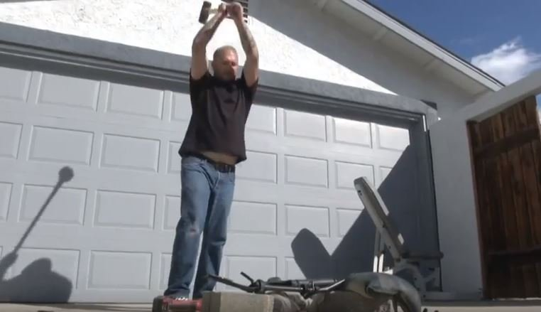 Chad Vachter smashes his AR-15 with a sledgehammer.