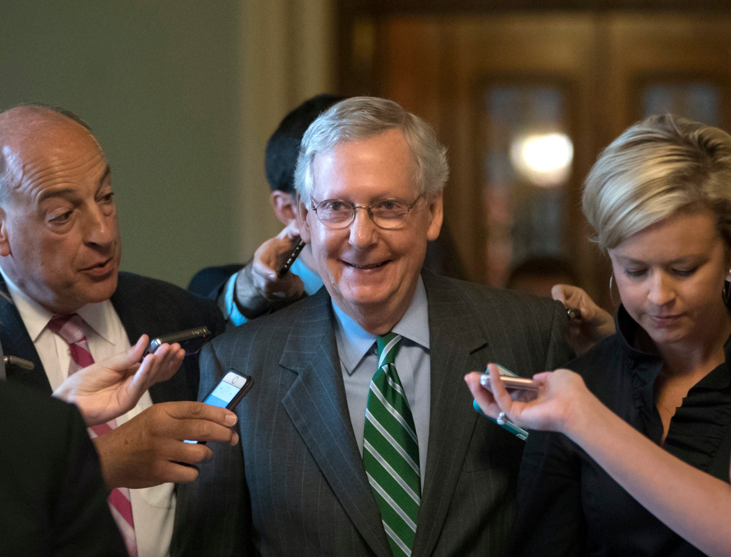 FILE: Sen. Mitch McConnell smiles as he leaves the chamber after announcing the release of the Republicans' healthcare bill on June 22, 2017.