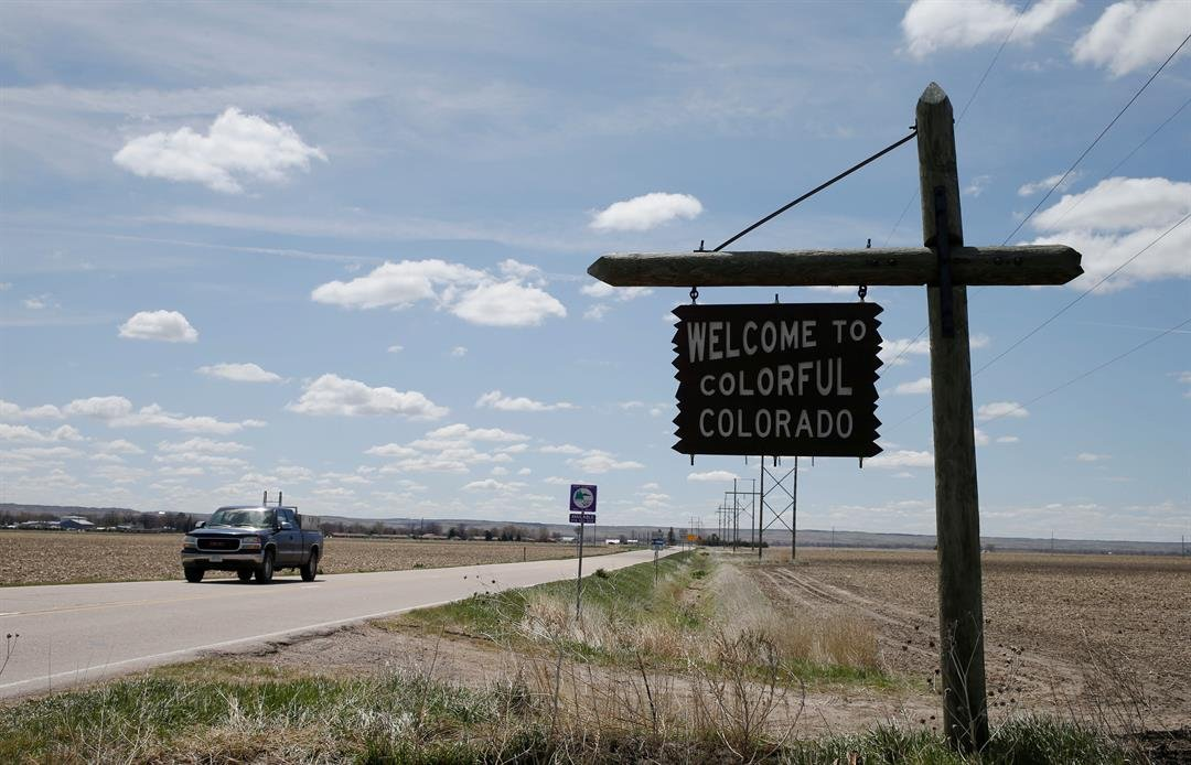 Pickup truck moves past the sign to welcome travelers to Colorado on the border with Nebraska just north of Julesburg, Colo., Thursday, April 21, 2016,