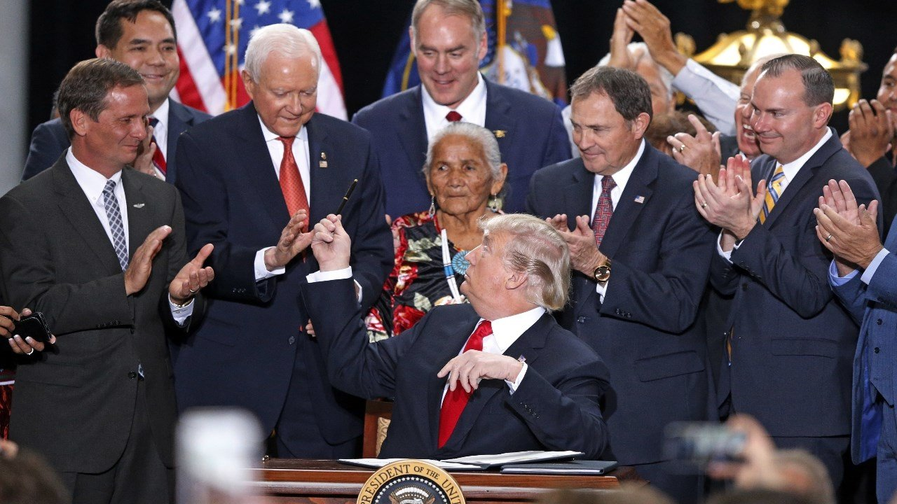 President Donald Trump hands a pen to Sen Orrin Hatch, R-Utah, after signing a proclamation to shrink the size of Bears Ears and Grand Staircase Escalante national monuments at the Utah State Capitol Monday, Dec. 4, 2017 (AP Photo/Rick Bowmer)