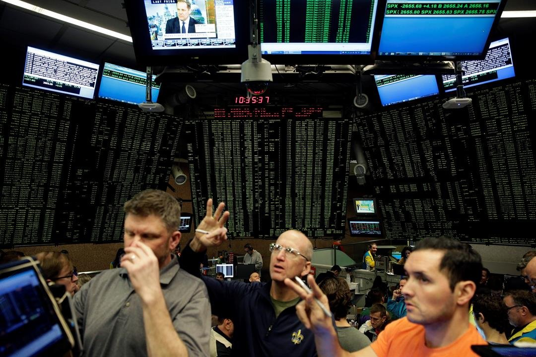 Traders work in a trading pit at the Chicago Board Options Exchange, Monday, Dec. 11, 2017, in Chicago, as they trade S&P 500 Options, unrelated to bitcoin futures. Trading in Bitcoin futures began Sunday on the CBOE. (AP Photo/Kiichiro Sato)