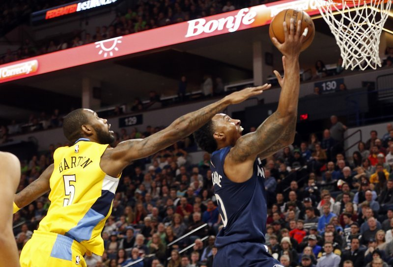 Minnesota Timberwolves' Jeff Teague, right, lays up as Denver Nuggets' Will Barton defends in the first half of n NBA basketball game Wednesday, Dec. 27, 2017, in Minneapolis. (AP Photo/Jim Mone)
