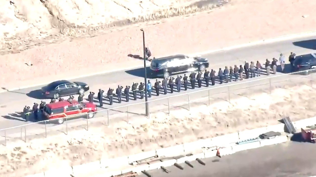 Law enforcement and firefighters salute the body of a Douglas County Deputy killed in the line of duty on December 31, 2017.