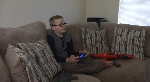 Sean Lloyd plays video games in his Colorado Springs home
