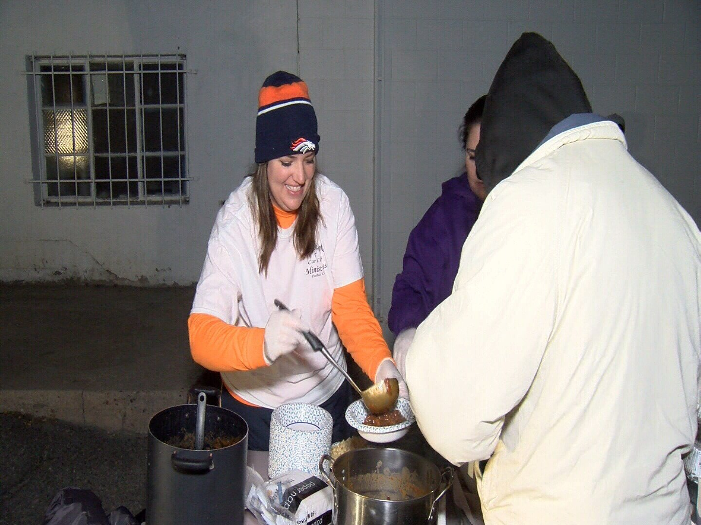 Members of Lord's Disciples Car Club serve food to homeless outside Salvation Army