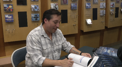 Jonathan Givens, a Doherty High School grad, signs books at Barnes & Nobel