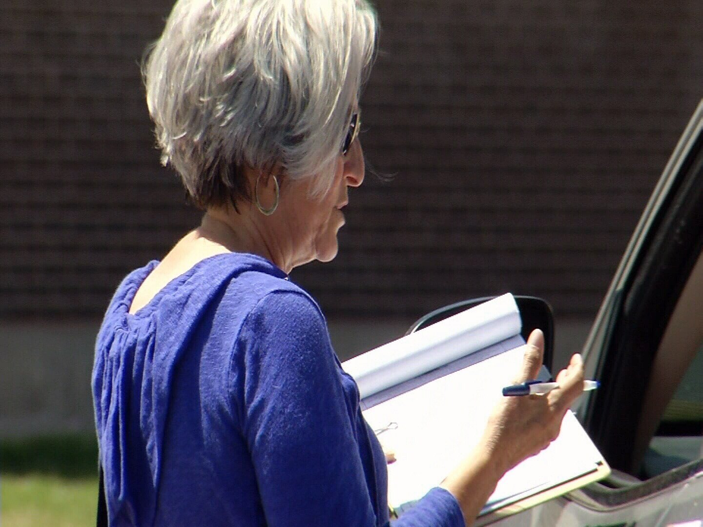 Carole Partin, a retired teacher, collects signatures for Initiative 93 from parents waiting to pick up their children from Roncalli Stem Academy in Pueblo