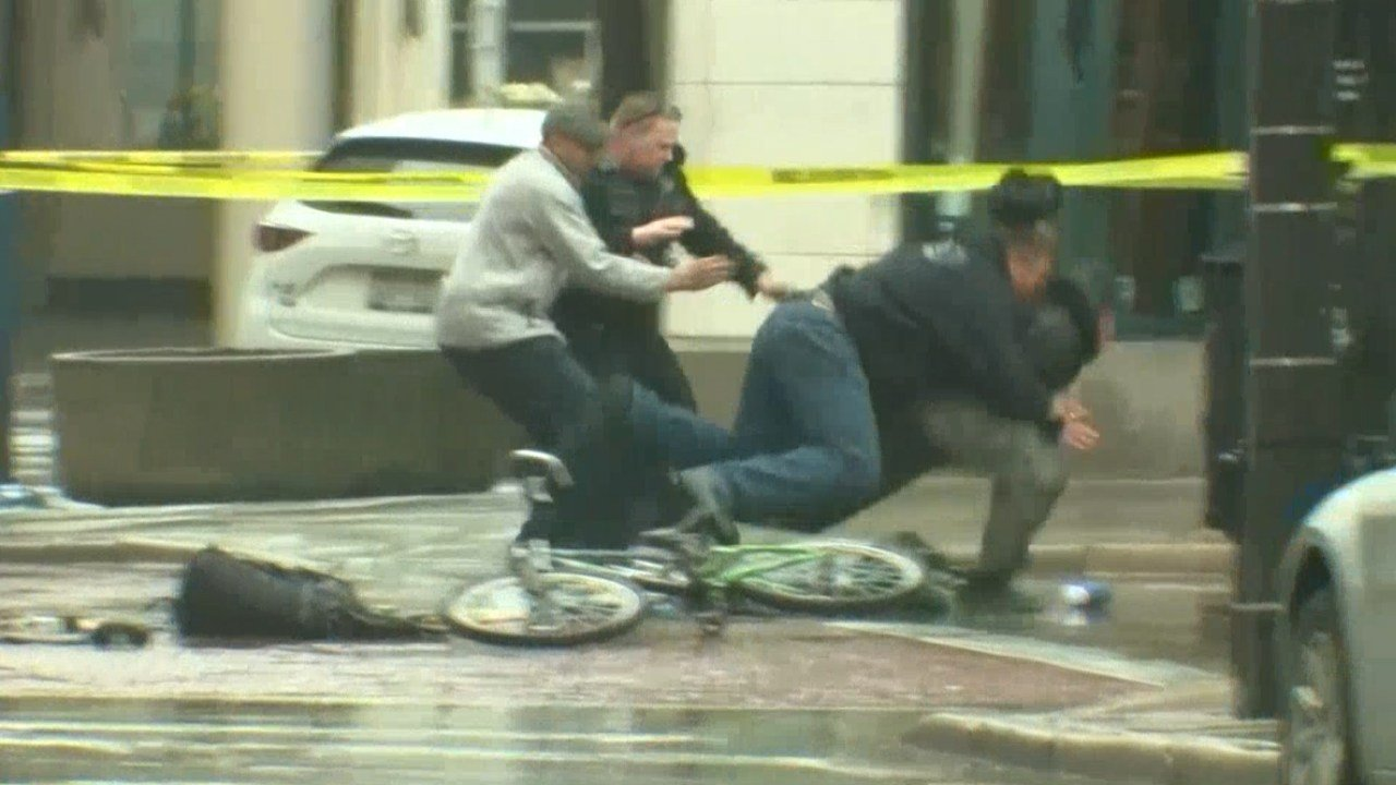 Police tackle a man who interfered with a suspicious package call. (NBC News)