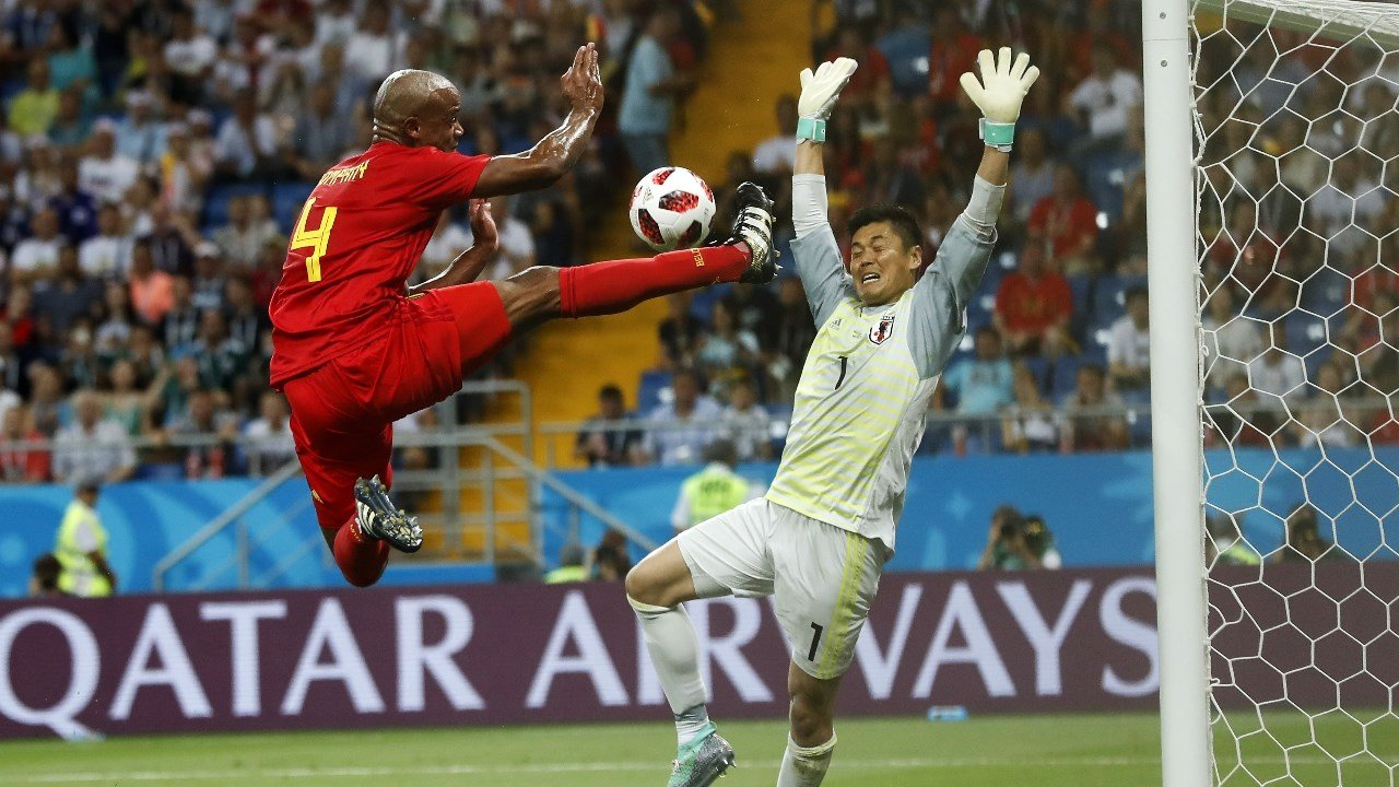 Belgium's Vincent Kompany jumps for the ball in front of Japan goalkeeper Eiji Kawashima. (AP Photo/Petr David Josek)