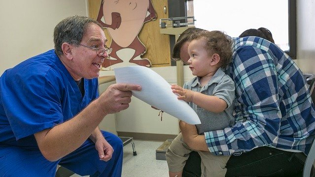 Pediatrician Charles Goodman, left, explains to Frank Fierro, the father of 1 year-old Cameron Fierro, the need of getting the measles-mumps-rubella vaccine, or MMR vaccine at his practice in Northridge, Calif., Thursday, Jan. 29, 2015 (Damian Dovarganes)