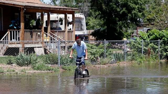 Anthony Harper ride his bike down a flooded street in Greeley, Colo., on Tuesday, June 3, 2014. (AP Photo/Ed Andrieski)