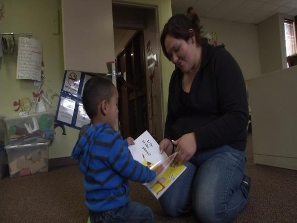 A 3-year-old boy reads with his mother at Catholic Charities of Pueblo