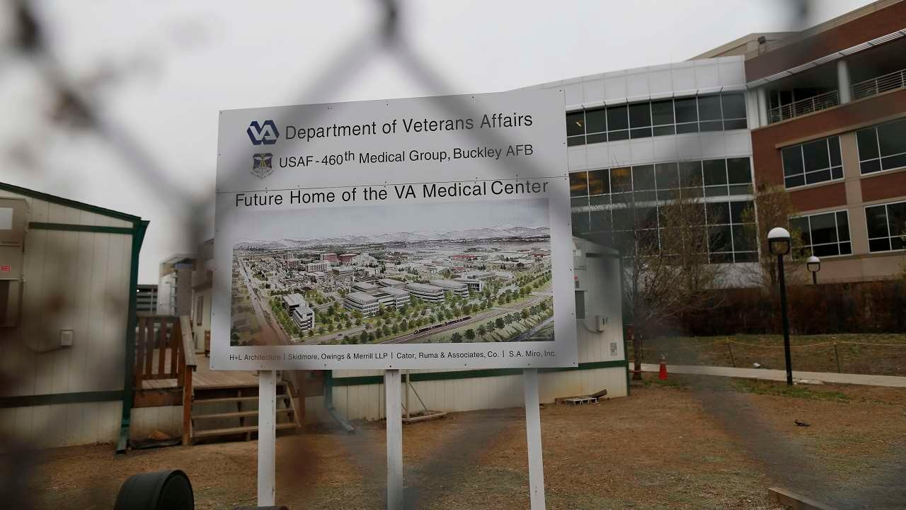 As seen through the pattern of a cyclone fence, a sign stands at the construction site of the Veterans Affairs hospital Thursday, April 2, 2015, in Aurora, Colo. (AP Photo/David Zalubowski)