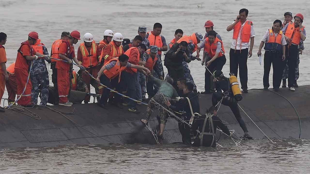 In this photo released by China's Xinhua News Agency, rescuers save a survivor, center, from the overturned passenger ship in the Jianli section of the Yangtze River in central China's Hubei Province Tuesday, June 2, 2015.