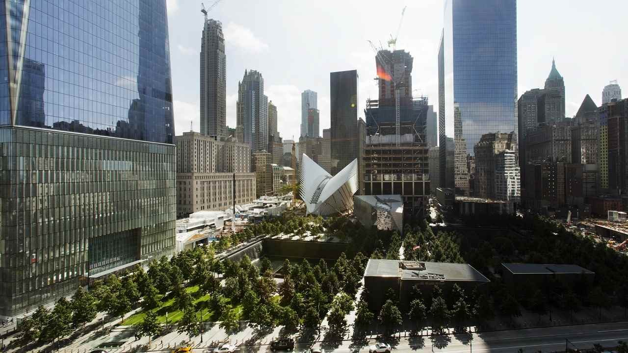 This Wednesday, Sept. 9, 2015 photo shows the National September 11 Memorial and Museum, center foreground, surrounded by One World Trade Center, left, the white v-shaped transportation hub, center, and 4 World Trade Center, the tall building at right, in