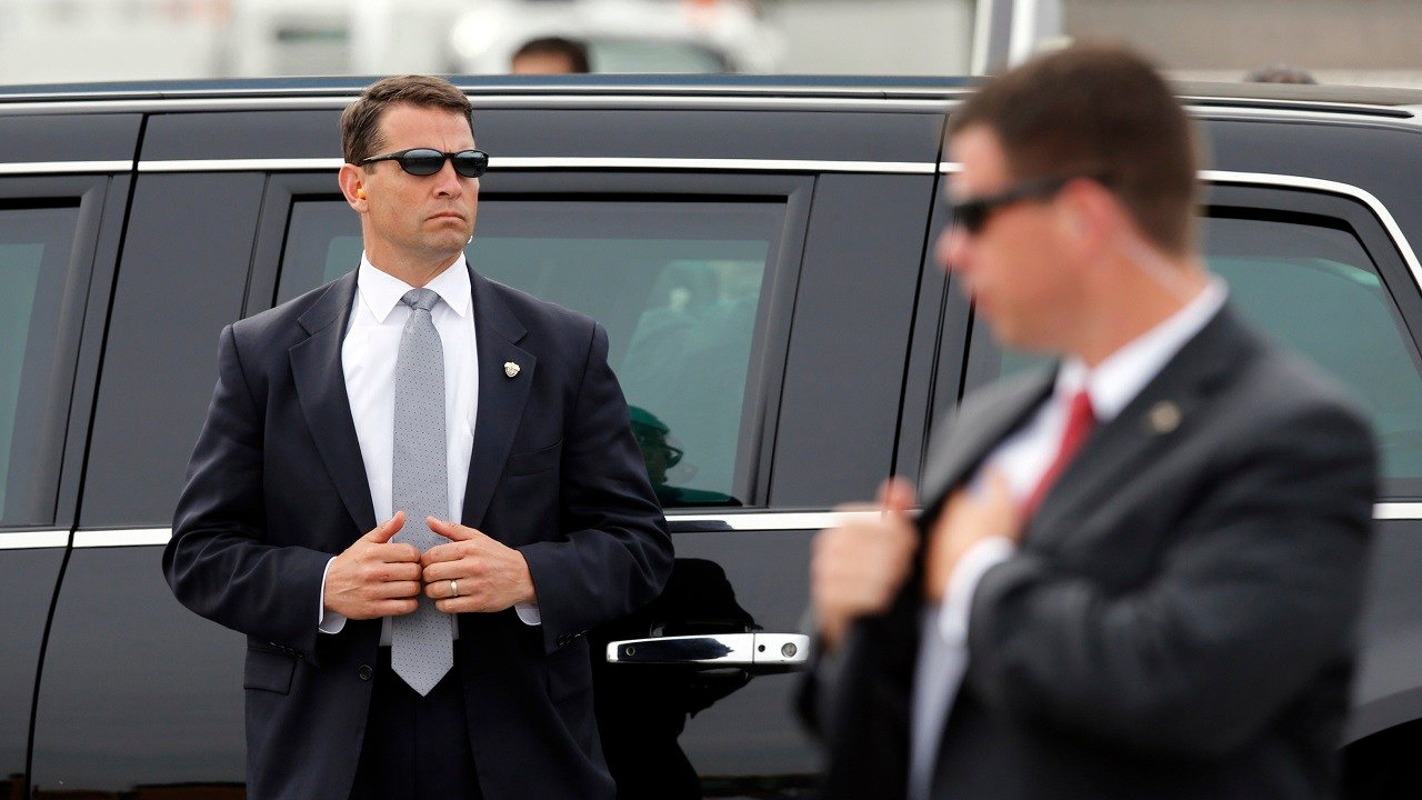 Secret Service agents stand guard outside the presidential limousine before President Barack Obama departed Westchester County Airport in Harrison, N.Y., Wednesday, May 20, 2015.