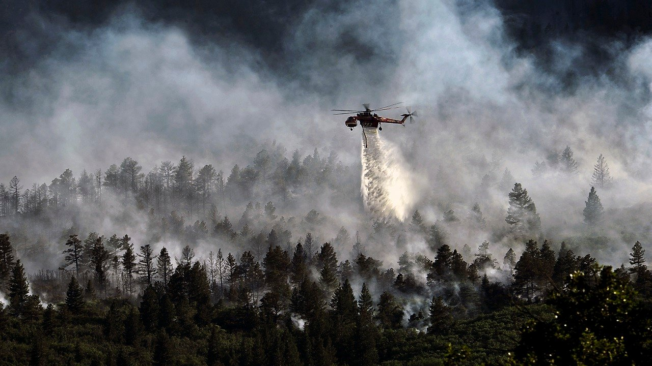 A helicopter drops water on the fire as firefighters continued to battle the blaze that burned into the evening hours in Waldo Canyon on the U.S. Air Force Academy June 27, 2012. (Master Sgt. Jeremy Lock USAF)