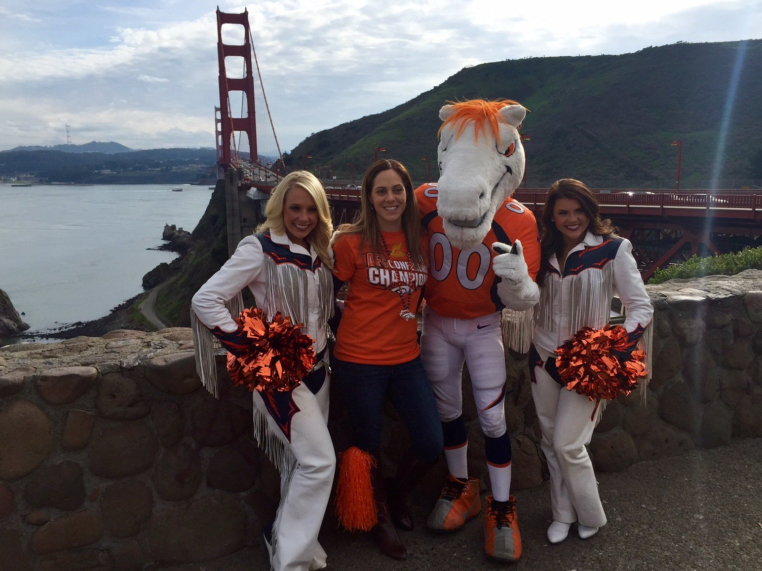 Miles the Mascot and Cheerleaders pose with a Broncos fan looking over the Golden Gate Bridge